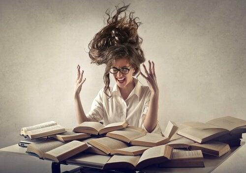kitap yığını arasında stresli bir kadın