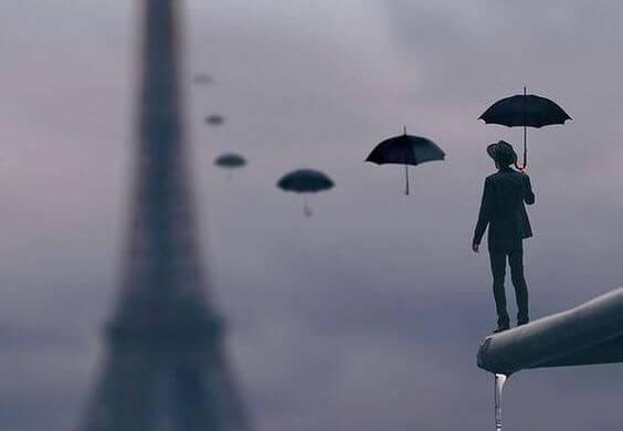 Elinde şemsiyesi ile Eyfel Kulesine bakan adam