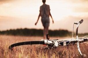 bisikletini bırakıp tarlada yürüyen kadın