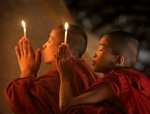 Ellerinde mum ile dua eden Budist çocuklar