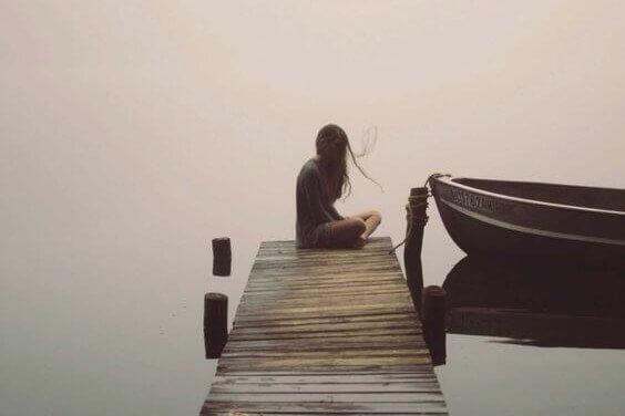 Su kenarındaki iskeleye oturmuş kadın