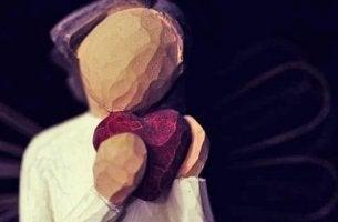elinde kalp tutan ahşap figür
