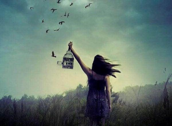 kafesteki kuşları serbest bırakan kadın