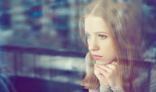 pencereden bakan düşünceli kadın
