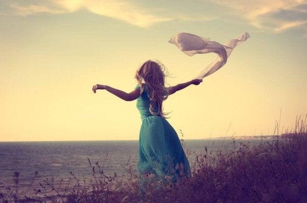 rüzgarda eşarp sallayan elbiseli kadın