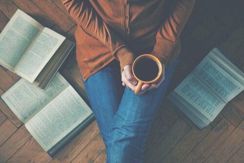 kitapların arasında kahvesiyle oturan kadın