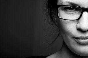 siyah beyaz fotoğrafta gözlüklü gülen kadın