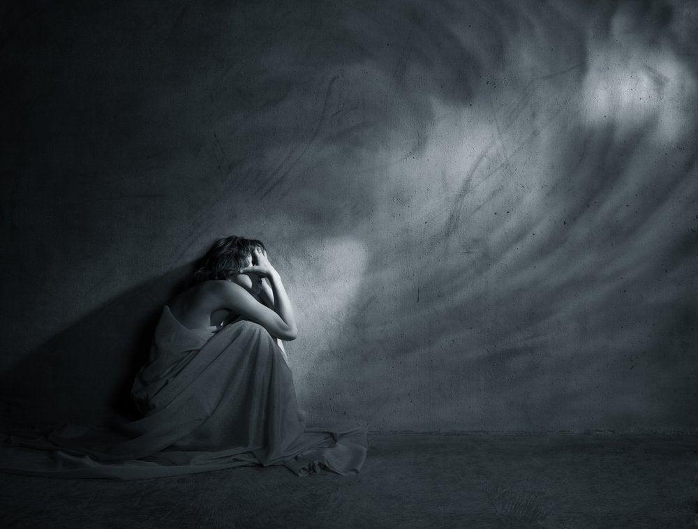 karanlık bir oda da depresyona girmiş kadın