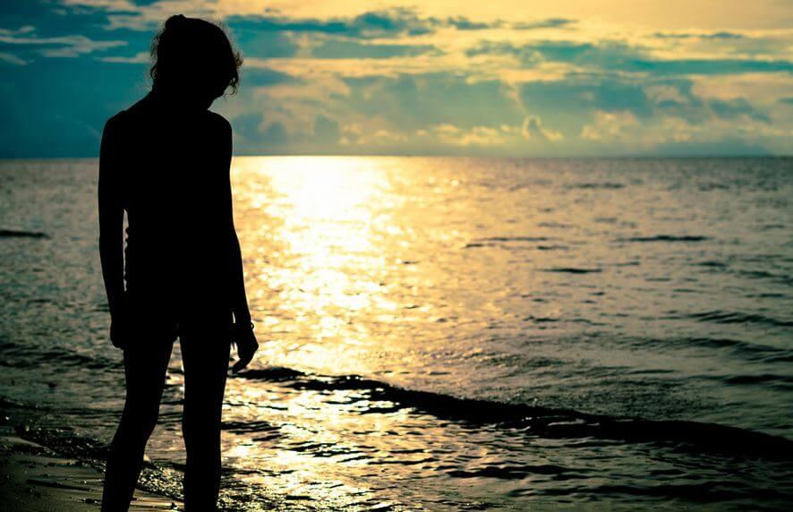 kumsalda tek başına duran kadın
