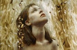 yapraklar arasından yukarı bakan kadın