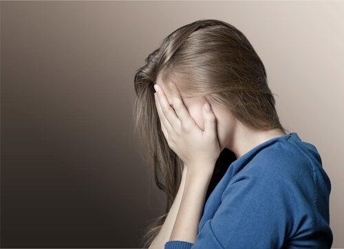 utanç içerisinde yüzünü eliyle kapamış kadın