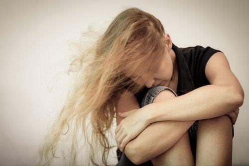 süklüm büklüm oturmuş depresyon kadını