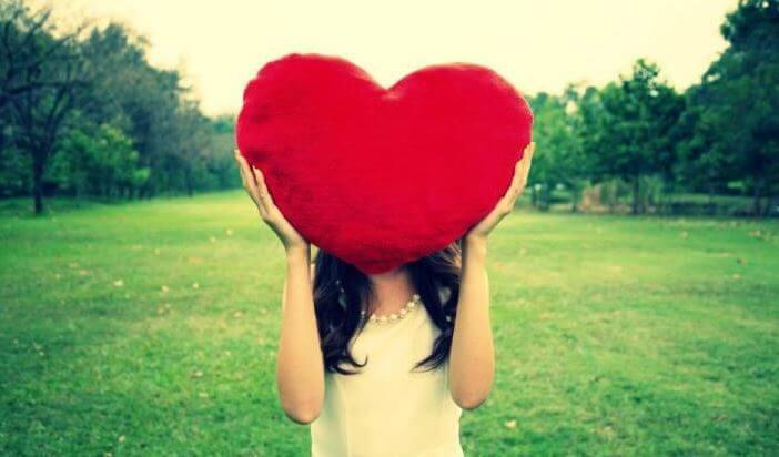 Ellinde kalp şeklinde bir yastık tutan kadın