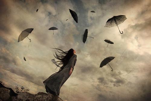 Fırtınalı havada uçan şemsiyelere bakan kadın