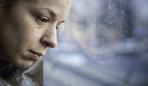 üzgün ve düşünceli anne başını cama yaslamış