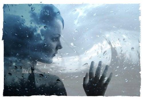 üzgün kadın ıslak pencerenin ardından bakıyor