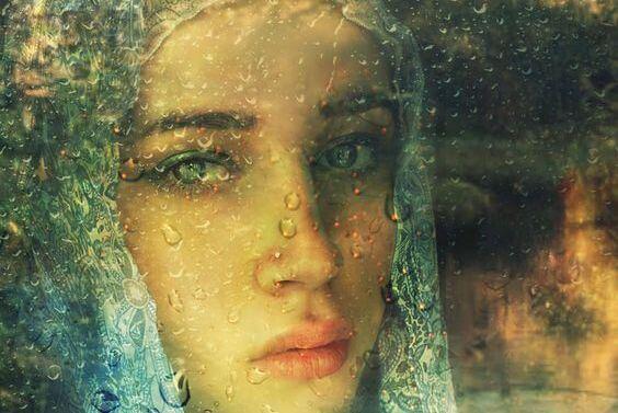 yağmur damlalı camın ardından bakan kadın