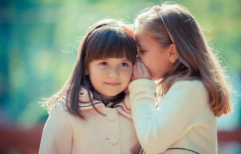 arkadaşının kulağına sırlarını fısıldayan küçük kız