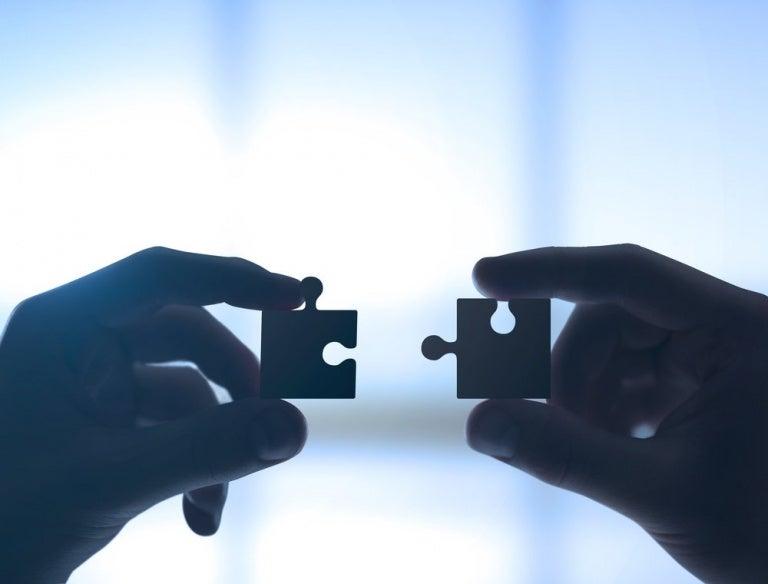 puzzle parçaları tutan eller