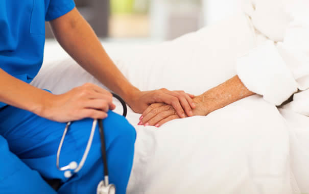 hastanın elini tutan hemşire