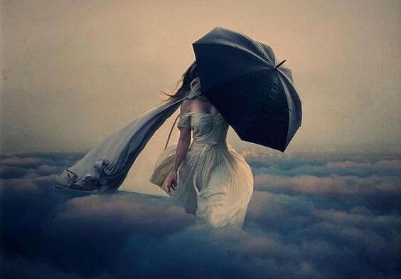 bulutların üzerinde yürüyen siyah şemsiyeli kadın