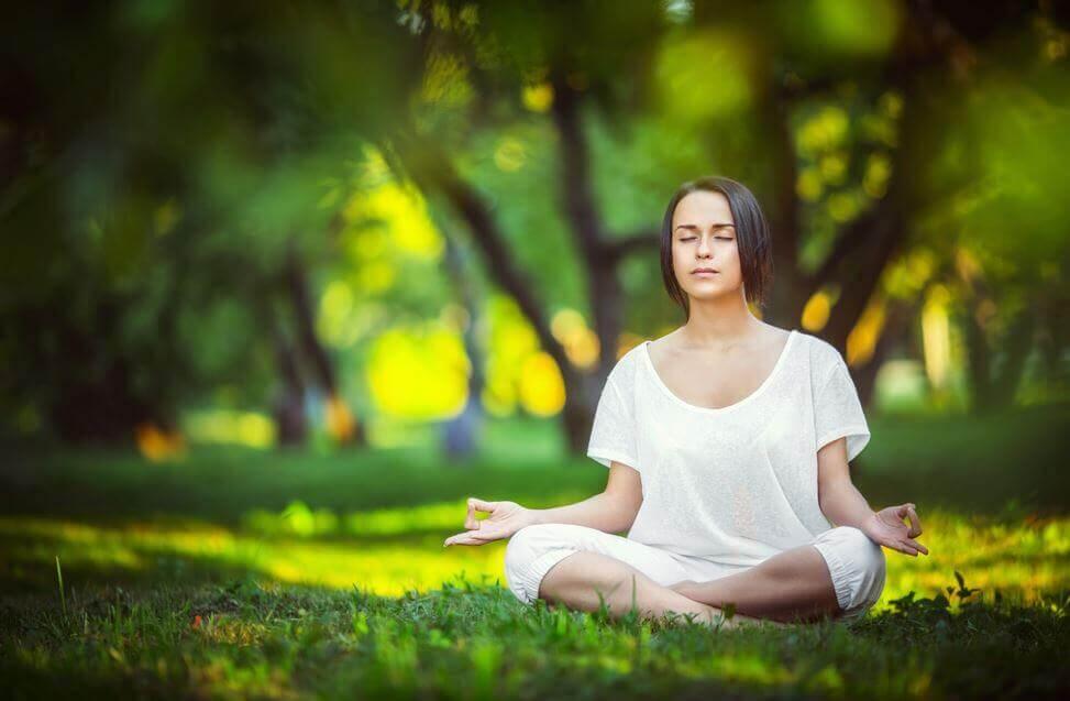 çimenlikte meditasyon yapan kadın