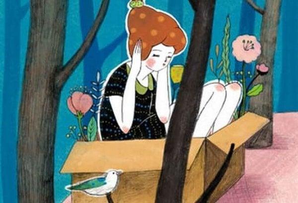 ağaç altında kutuda oturan kadın