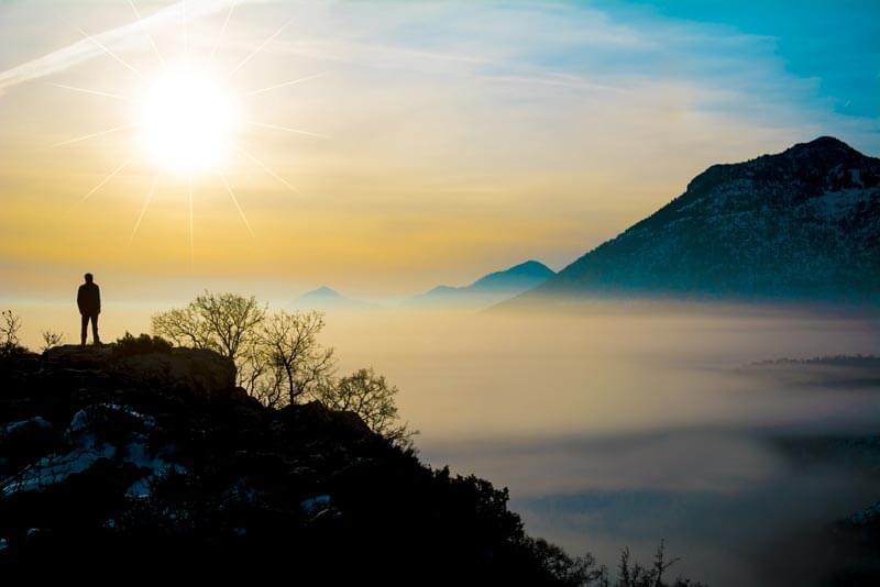 adam dağın tepesinden manzarayı izliyor