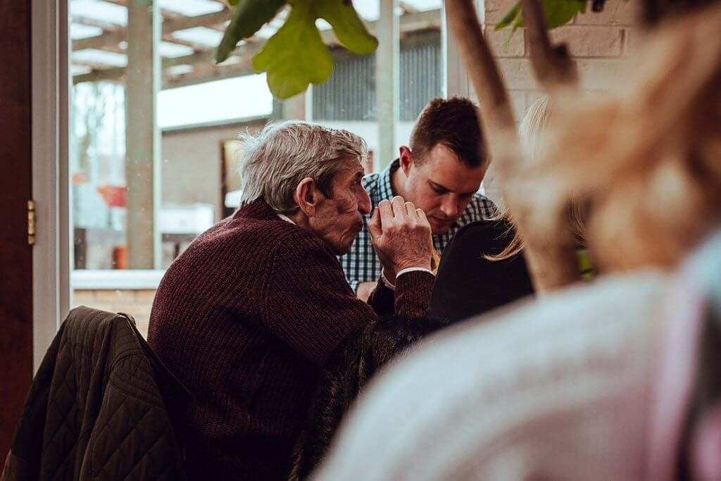 yaşlı adam masada yemek yiyiyor