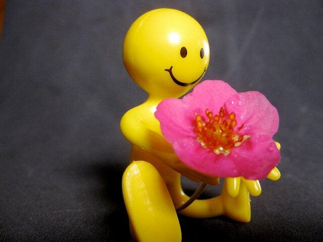 çiçek tutan sarı figür