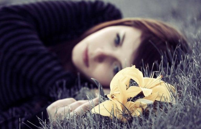 çimende yatan üzgün kız