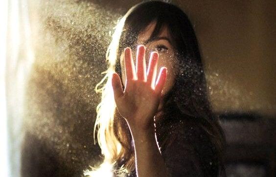 güneşi eliyle kapatan kadın