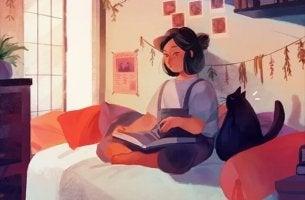 kadın odasında kedisiyle kitap okuyor