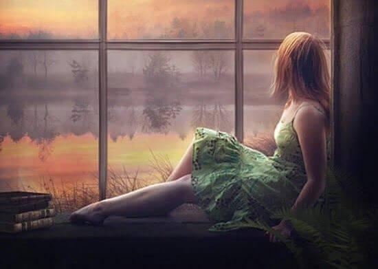 kadın pencereden gün batımı izliyor