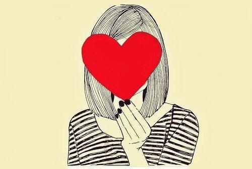 kırmızı kalp tutan kadın