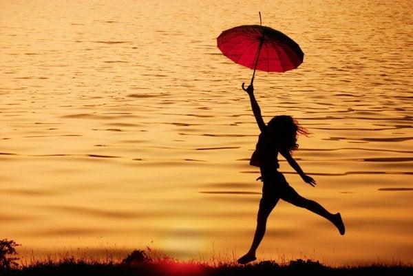 sahilde kırmızı şemsiyeli kız