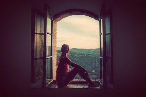 pencere kenarından manzaraya bakan kadın