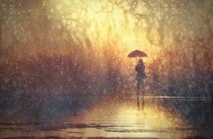 yağmurda yalnız başına duran kadın