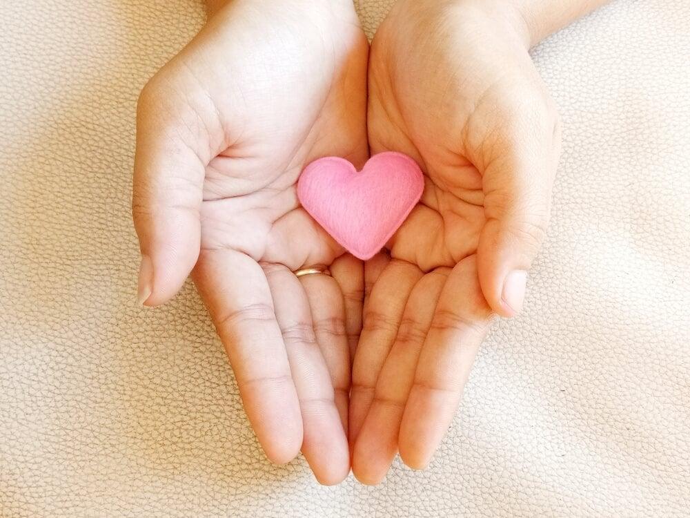 avuç içinde duran pembe kalp