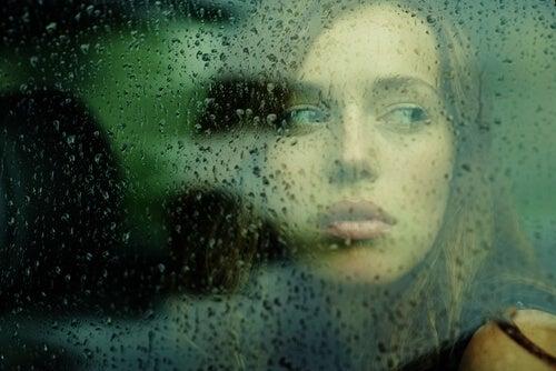 camdan bakan kadın ve yağmur damlaları