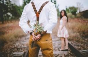 raylarda çiçek tutan adam