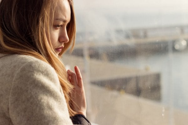 kadın üzgün bir şekilde camdan dışarı bakıyor
