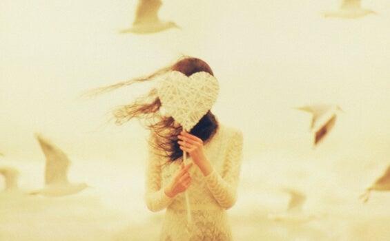 elinde beyaz kalp tutan kız