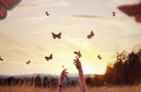 kelebekler ve gökyüzüne uzanan eller