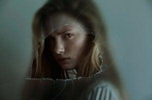 kırık camdan bakan sinirli kız