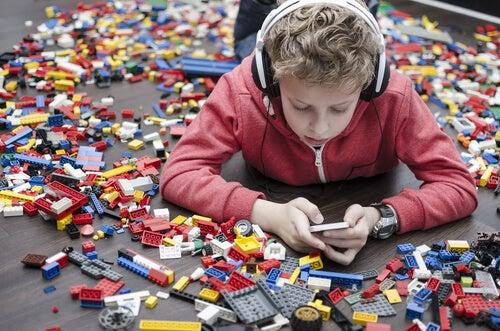 legoların ortasında telefondaki çocuk