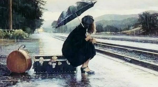 yağmurda tren bekleyen kadın