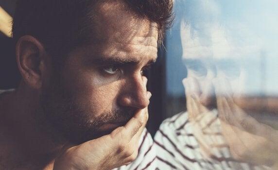 pencereden bakan düşünceli adam