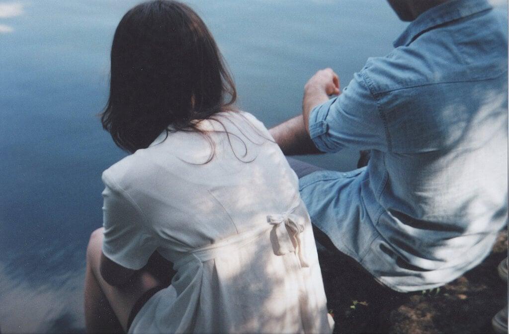 adam ve kadın deniz kenarında oturuyor