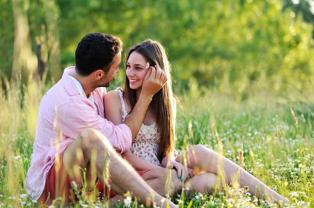 çimenlikte mutlu mutlu oturan çift